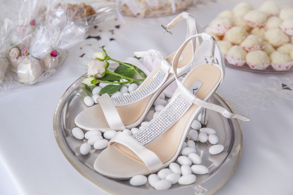 scarpe da sposa su vassoio pieno di confetti