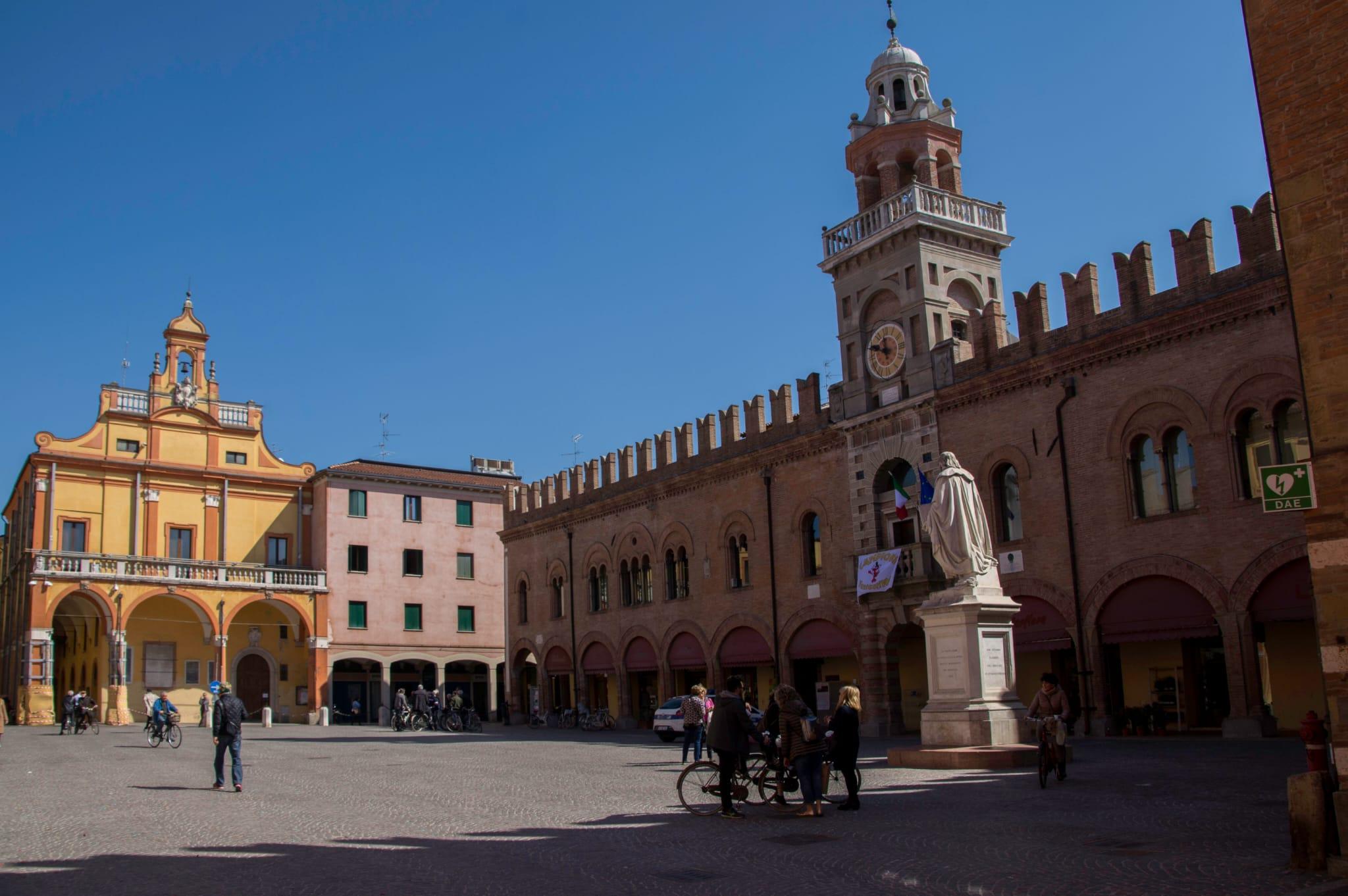 piazza con statua di cento con turisti