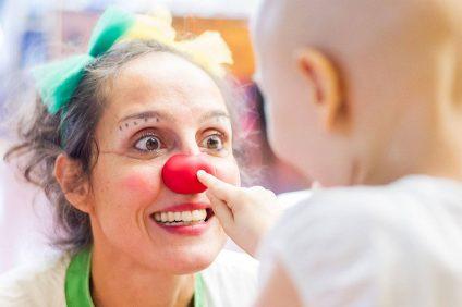 bambini - bambino che tocca il naso rosso di un dottore vestito da clown