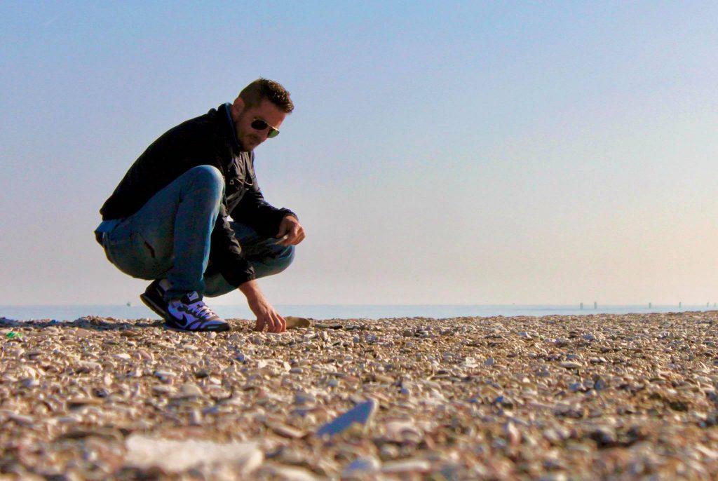Stefano raccoglie i sassi sulla spiaggia