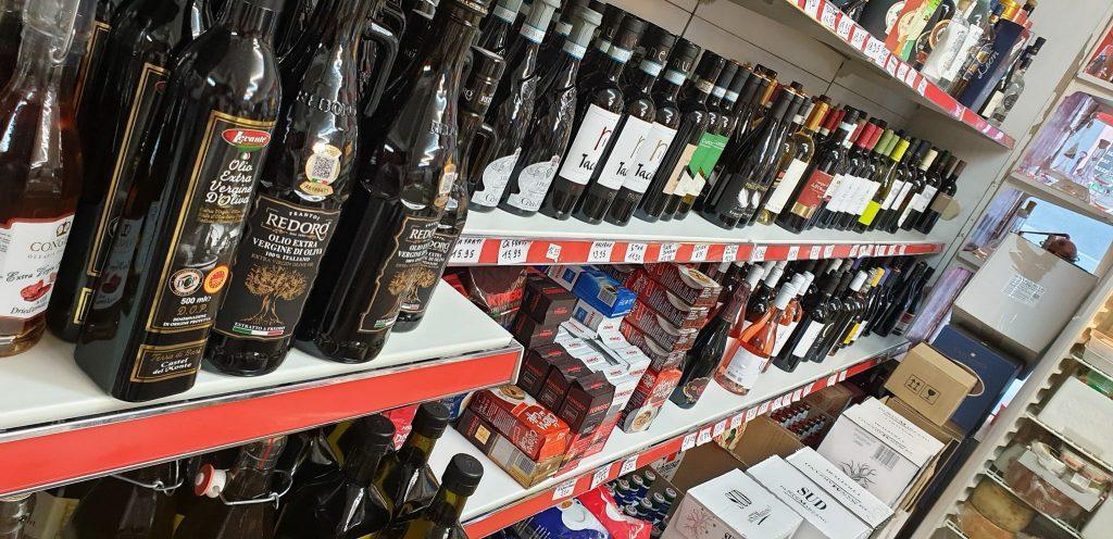 Scaffale con bottiglie di olio e vino