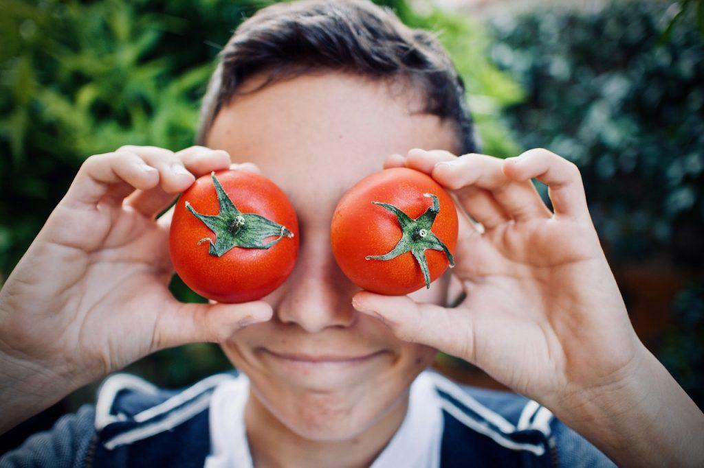 bambino con due pomodori vicino agli occhi