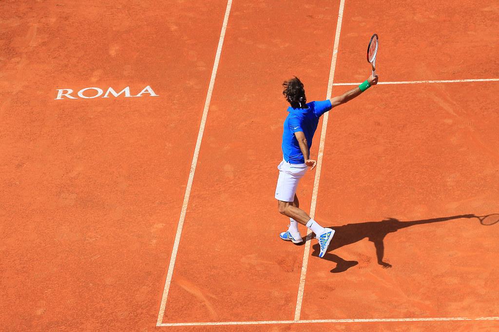 Un tennista durante una partita mentre colpisce la pallina durante gli internazionali di tennis