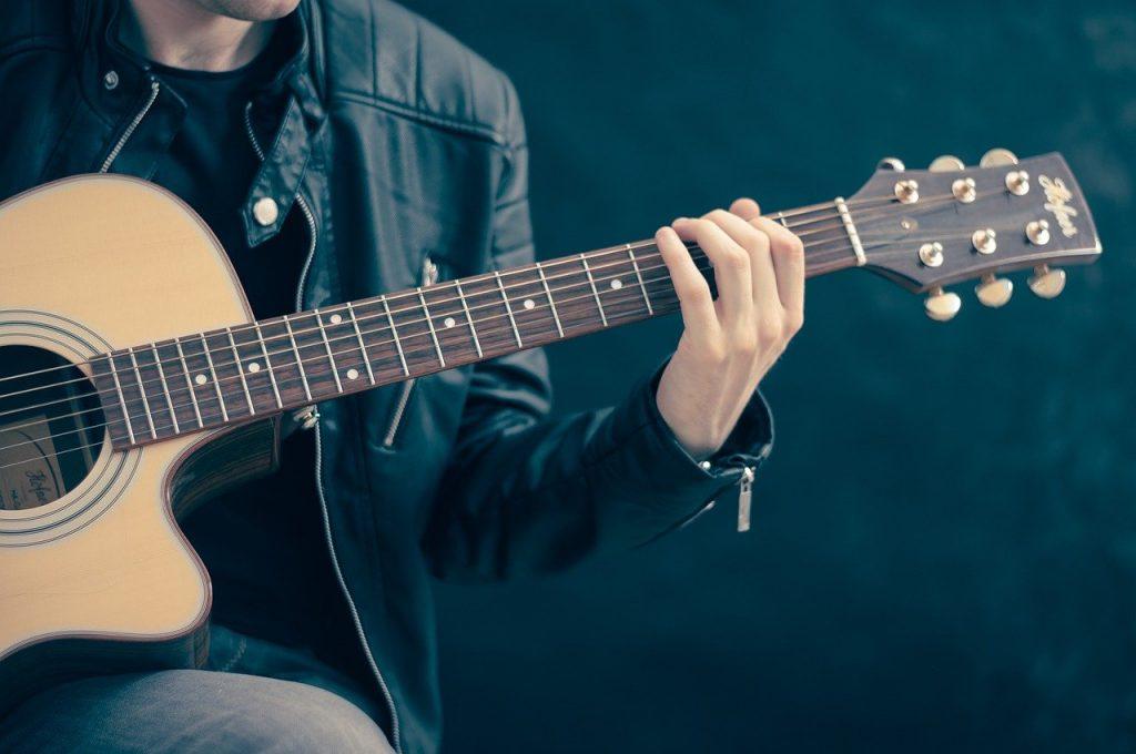 ragazzo suona alla chitarra delle canzoni d'amore