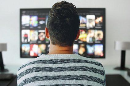Film da guardare durante il coprifuoco - Uomo che guarda catalogo Netflix in TV