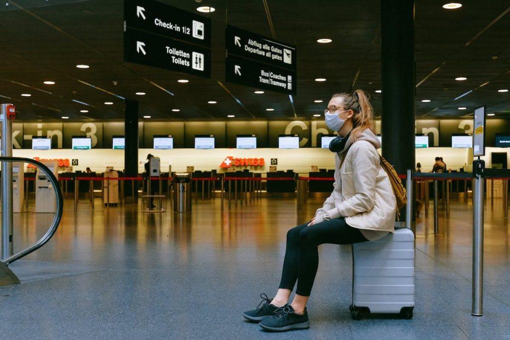 Passaporto sanitario digitale - ragazza con mascherina in aeroporto seduta sulla propria valigia