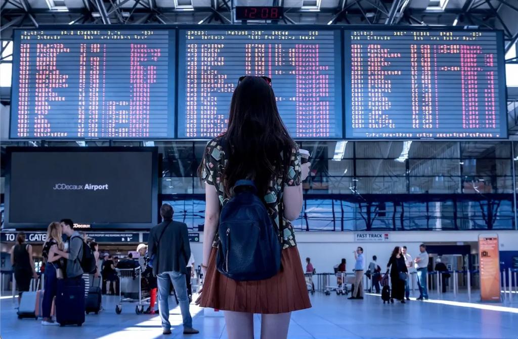 Passaporto sanitario digitale - ragazza guarda tabellone partenze in aeroporto