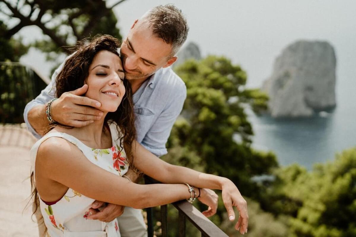 luna di miele in Italia - Coppia si abbraccia con lo sfondo dei faraglioni di Capri