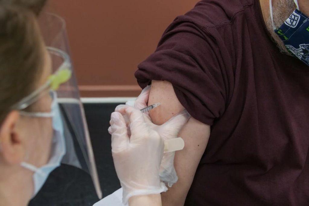 vaccini antiCovid in farmacia - Paziente in maglietta marrone riceve vaccino contro il Covid-19
