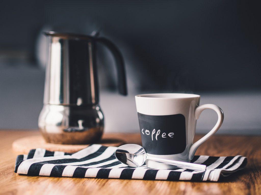 Tazza di caffè accanto ad una caffettiera