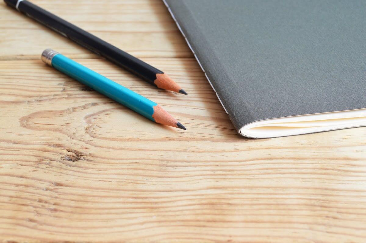 Olimpiadi di italiano - tavolo in legno con quaderno e due matite