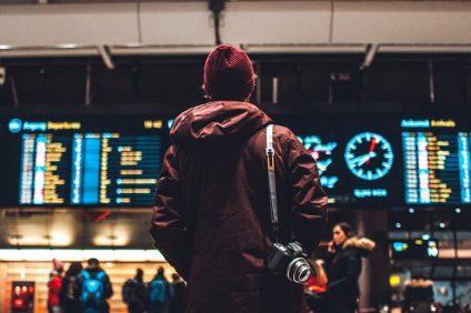 Travel Ban Stati Uniti - Ragazzo di spalle controlla gli orari di partenza e arrivo dei voli all'aeroporto
