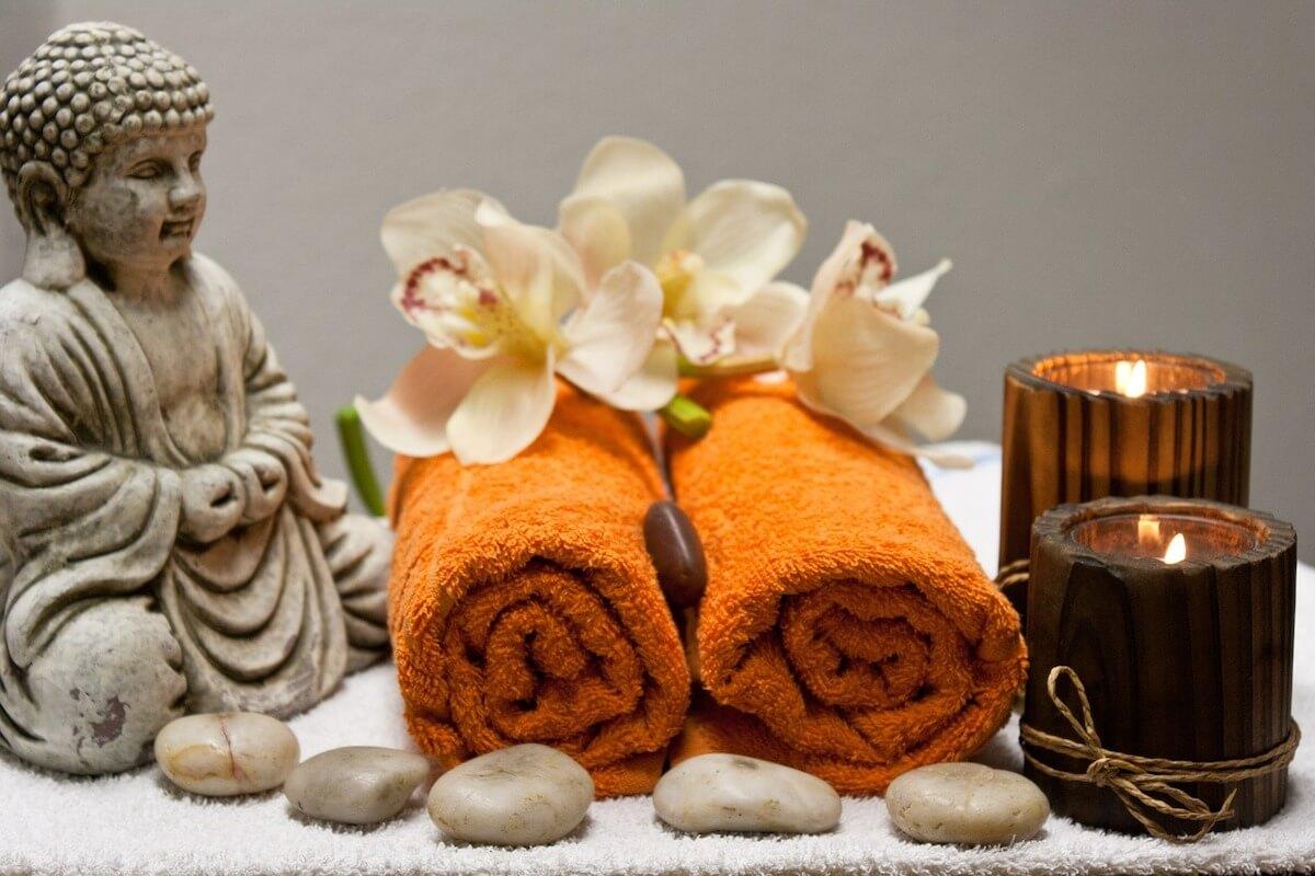 Bonus terme - due asciugamani arancioni con statua di Buddha, fiori, pietre e candele