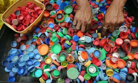 Mundo - Persona reciclando tapitas