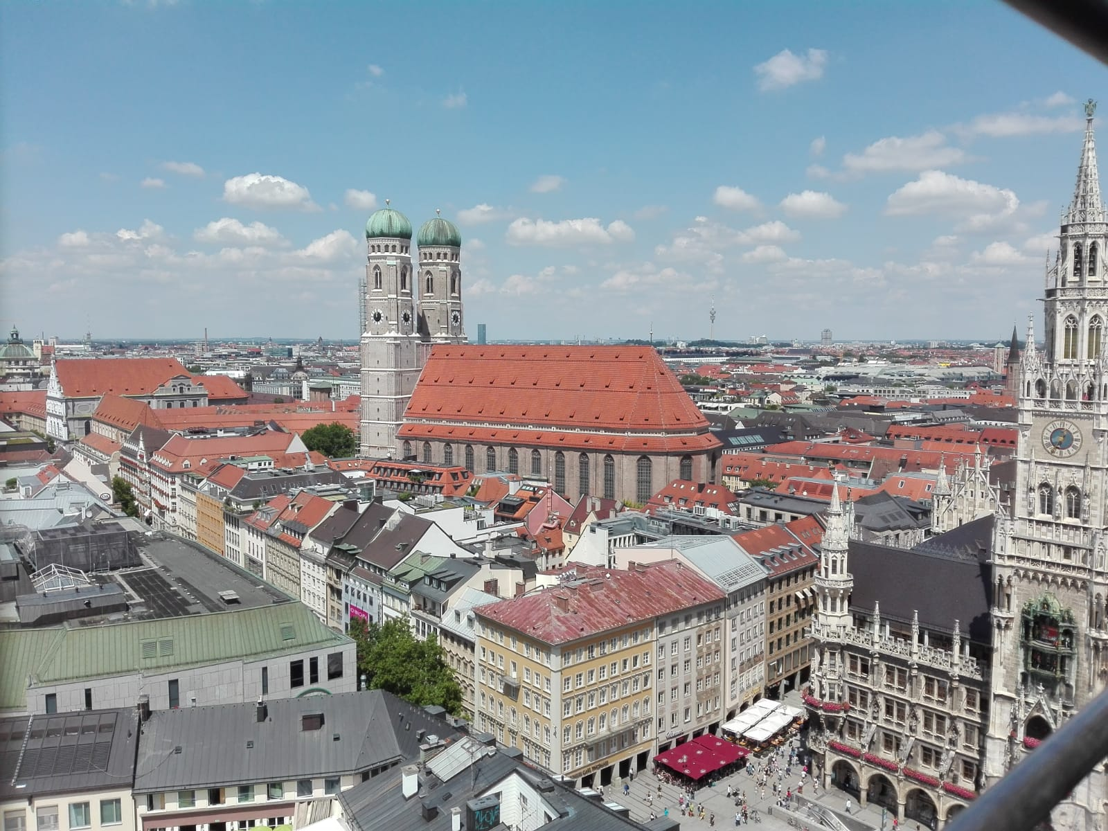 La foto mostra una veduta dall'alto della cattedrale di Monaco di Baviera, Frauenkirche. In particolare, risaltano i campanili con cupole a cipolla.