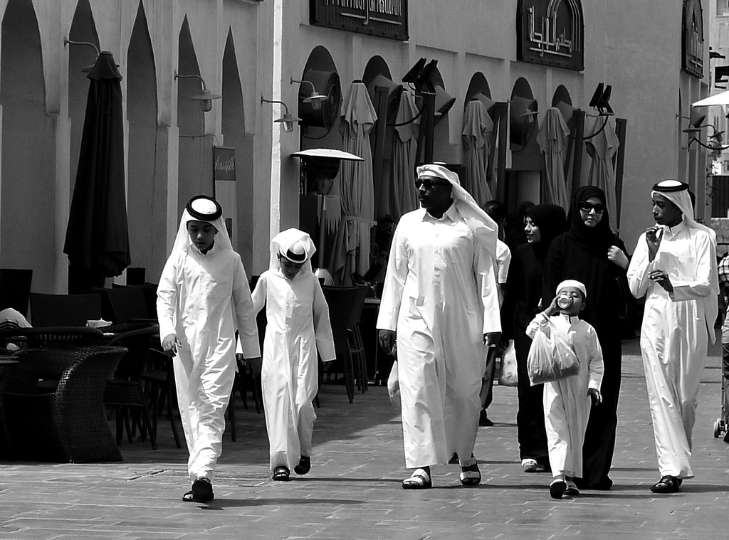 comportamenti - foto in bianco e nero di una Famiglia del Qatar che cammina per la strada