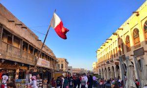 cosa visitare a Doha - souq di Doha con bandiera, negozi e gente in strada